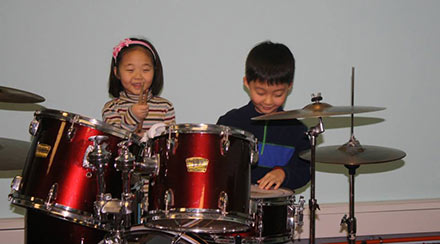 Two children playing drums